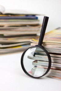 Magnifying lens on the background of the stack of magazines